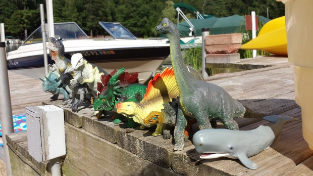Dinosaurs waiting for a boat ride in very orderly fashion.