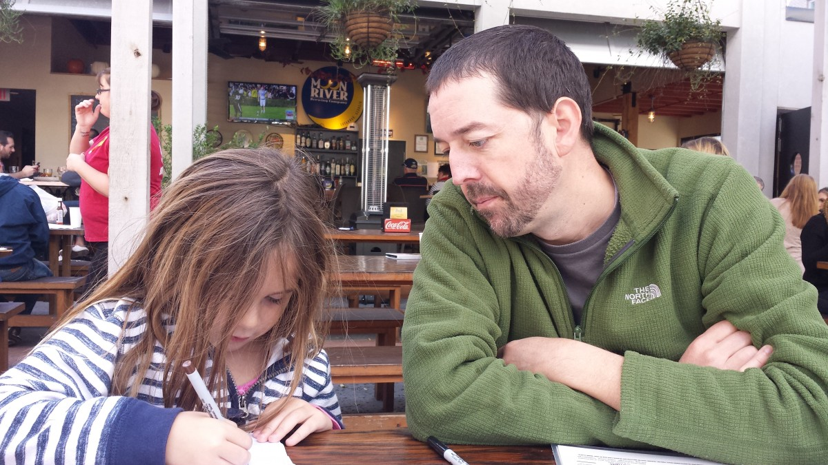 Papa Looks on as Luna Works on Her Giraffe Drawing at Moon River Brewing.